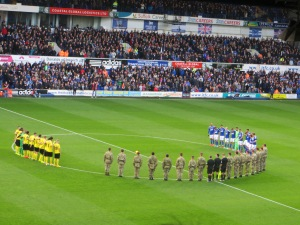 The players are joined by servicemen for the minute's silence
